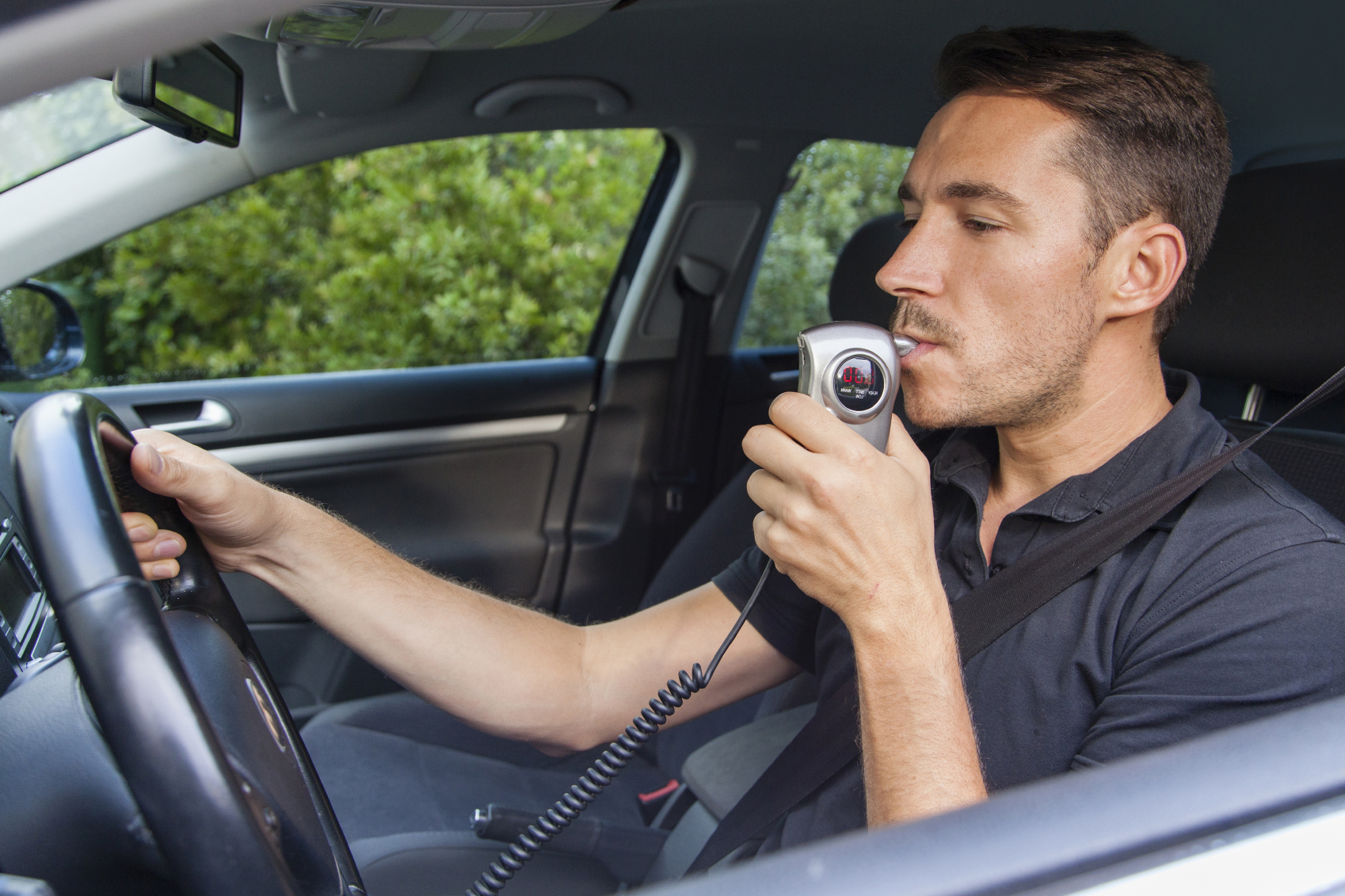 A man blows into an alcohol ignition interlock device. (stock image)