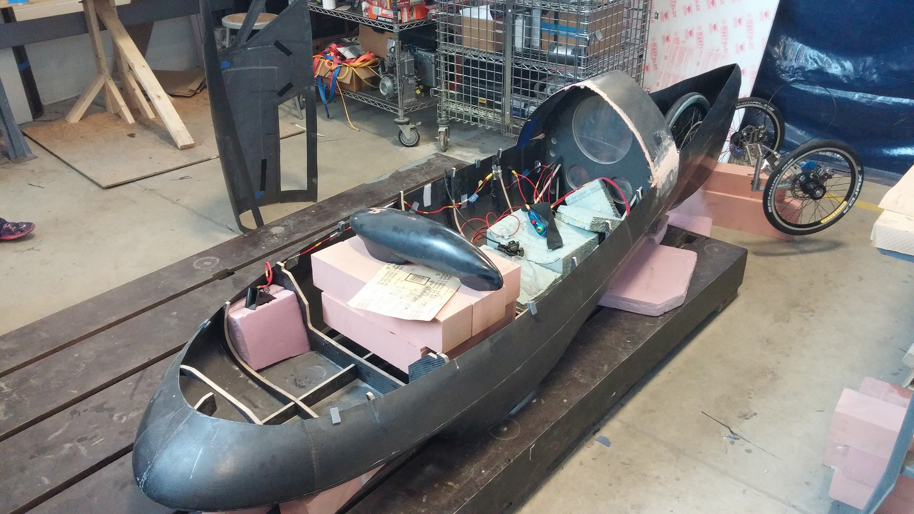 The carbon fiber body and exposed cockpit of the team's vehicle, under  construction inside the Wilson Student Project Center. Image courtesy: Supermileage Team