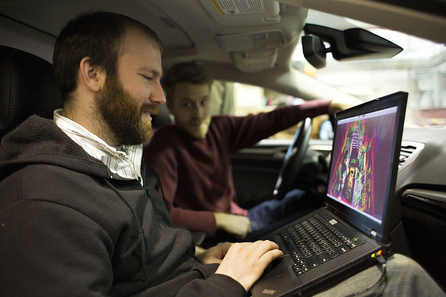 Schuyler Cohen, Engineer in Research, and Ryan Wolcott, Computer Science & Eng PhD Student, discuss the false-color map system generated by the new Automated Ford Fusion. Image credit: Joseph Xu