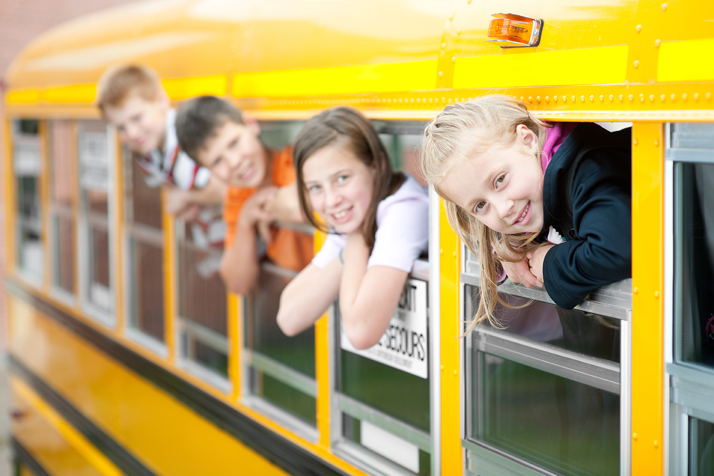 School children lean out of school bus windows. (stock image)