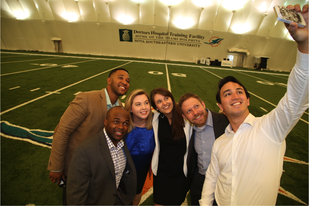 University of Michigan Ross MBA students take a selfie on the 50-yard line at the Miami Dolphins training facility in Davie, Fla., L-R: C.J. Azubuine (foreground), Darryl Tricksey, Aimee Grimshaw, Alexa Likens, Jeffrey Gross and John Thompson. Image credit: Angel Valentin