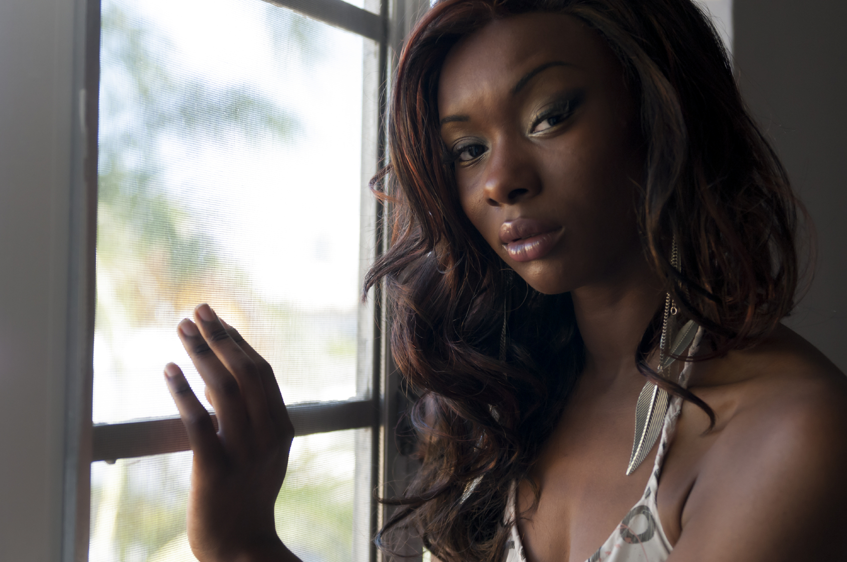 An African American woman standing at a window and looking at the camera. (stock image)
