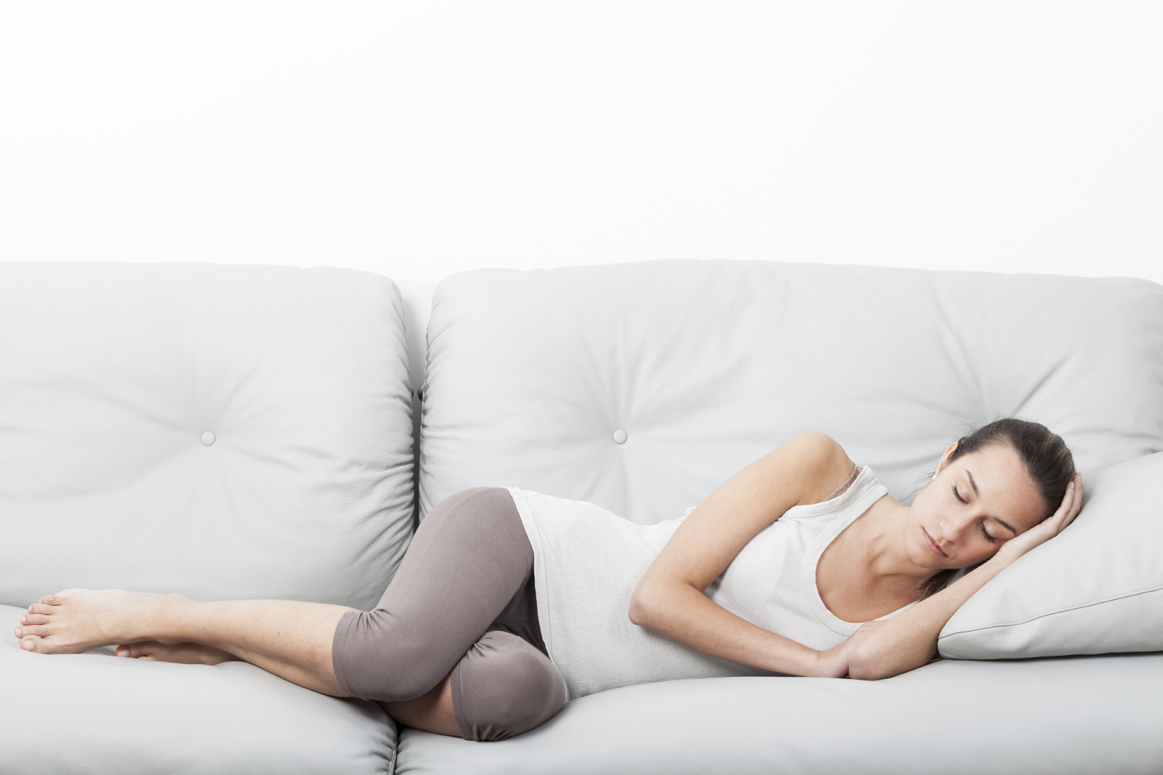 A woman sleeping on a couch. (stock image)