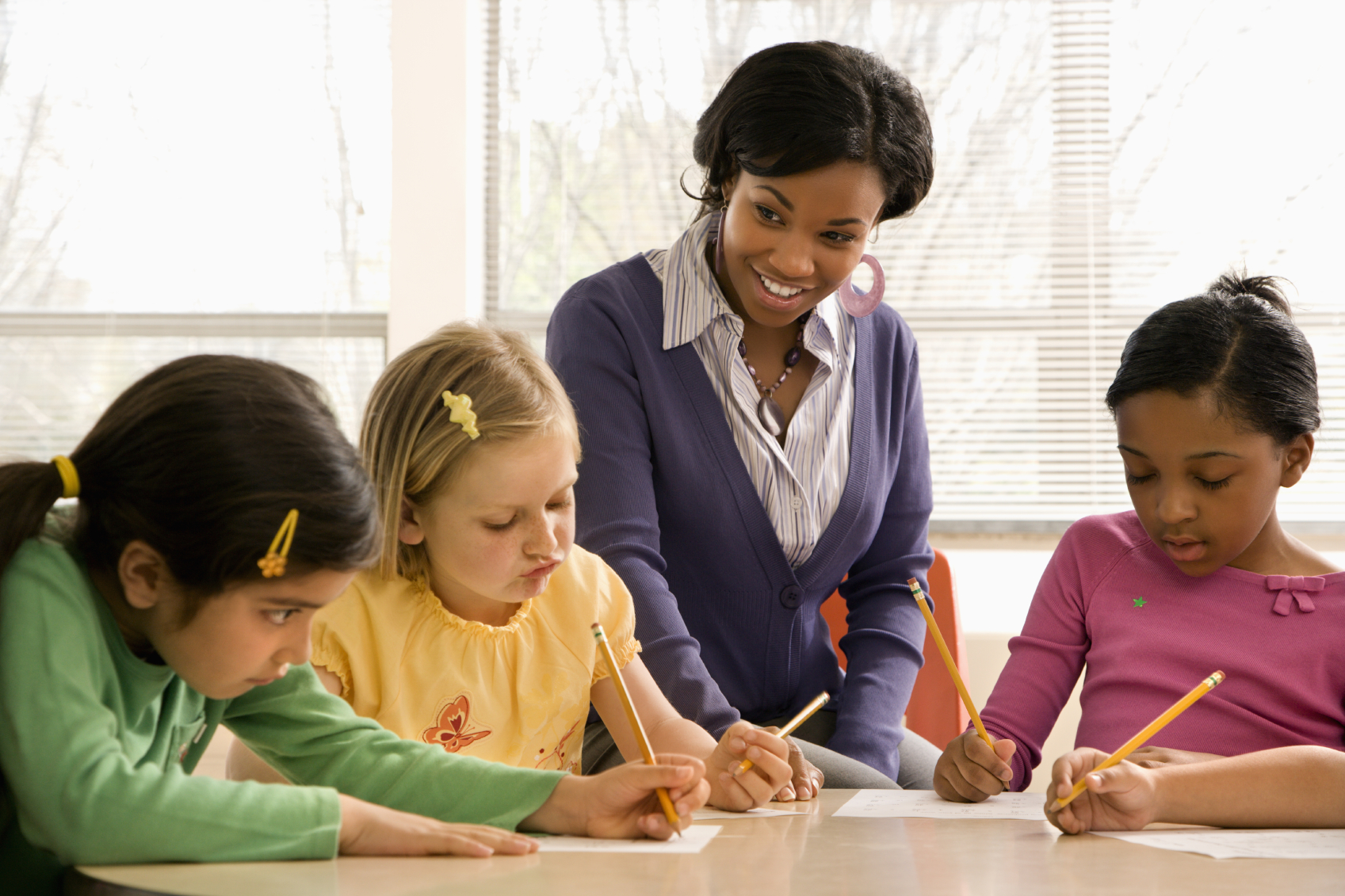 A student collaborating with elementary school students. (stock image)