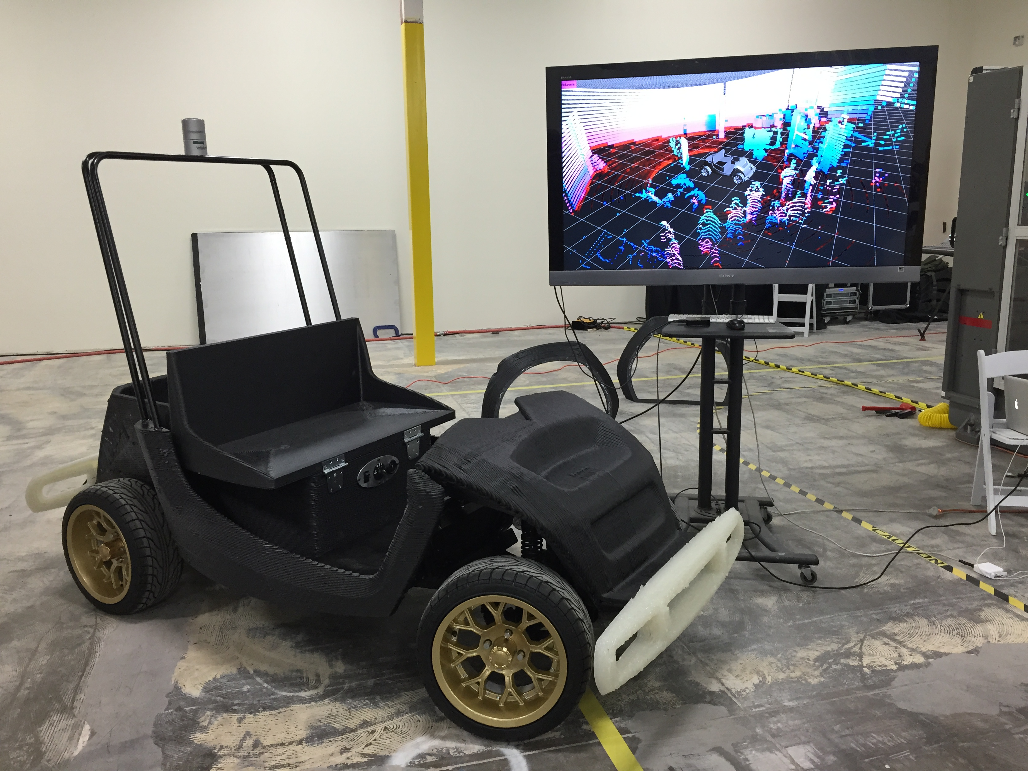 Researchers at the University of Michigan will develop autonomous capabilities for this 3-D printed low-speed electric vehicle that's manufactured by Arizona technology company Local Motors. The screen in the background shows a laser scan of the room. Image credit: Local Motors