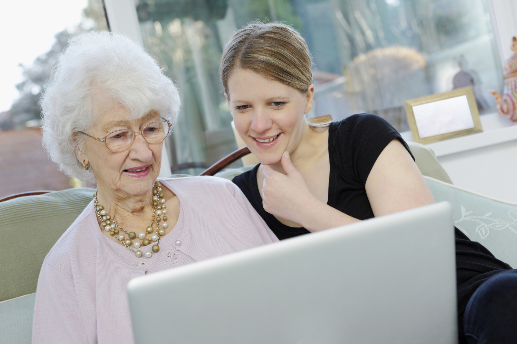 Young woman with her grandmother working on laptop at home. (stock image)