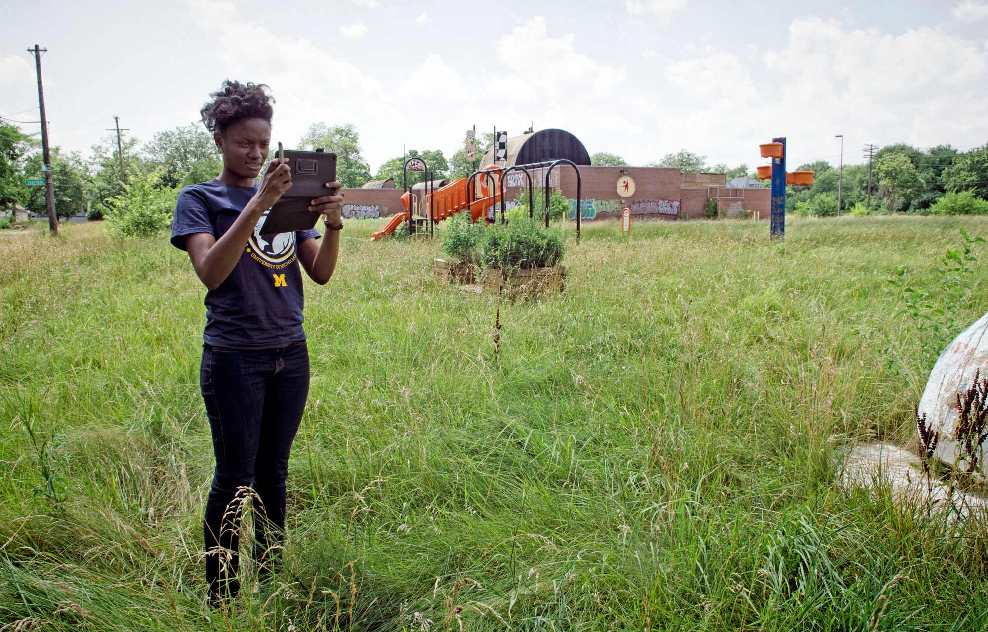 Jasmine Omeke photographs footpaths across an abandoned school yard, in the Detroit's East side in 2013. Image Credit: Dave Brenner/SNRE