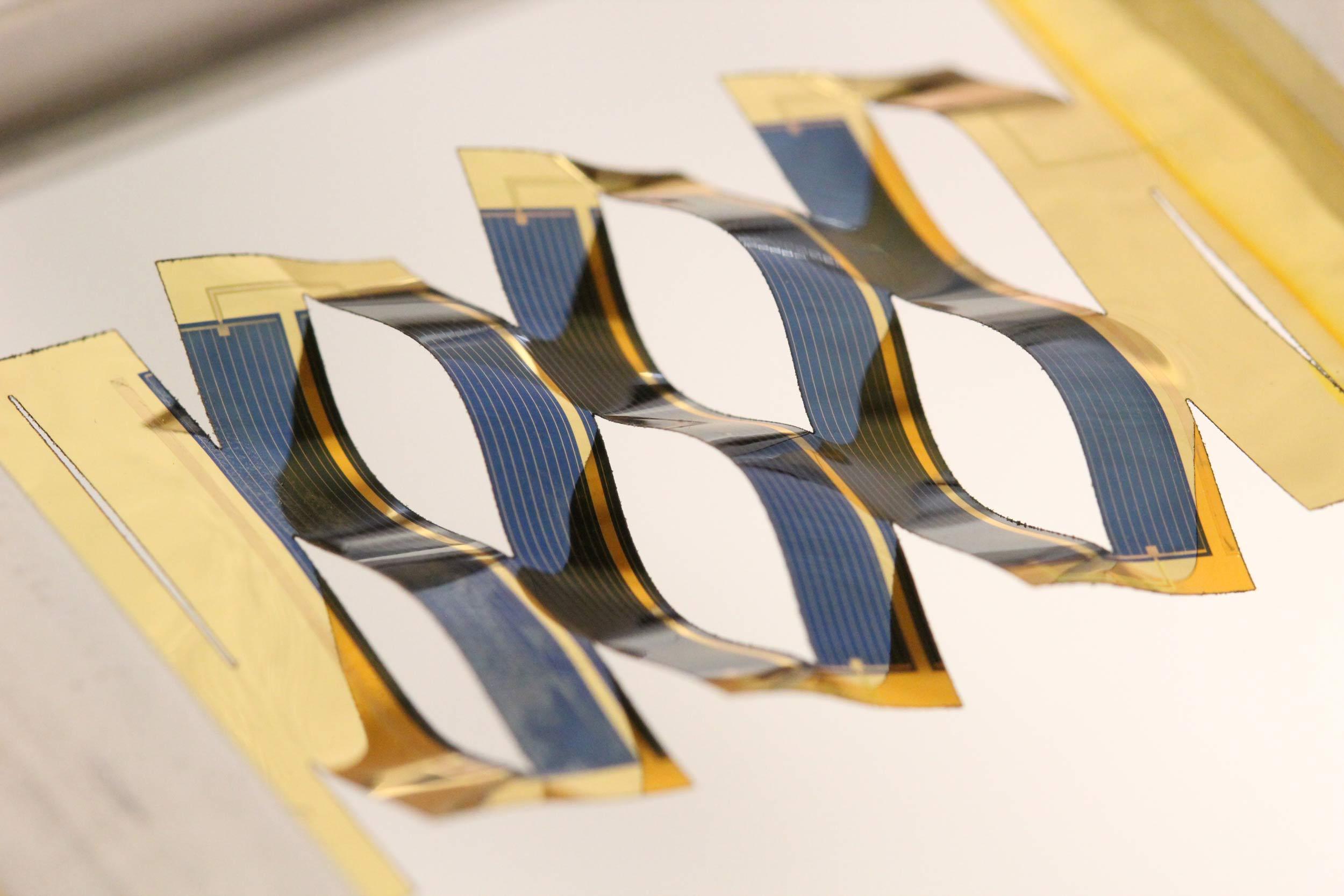 密歇根大学的研究人员将日本剪纸艺术应用到太阳能电池板的设计中,让后者能够追踪阳光。一块扁平的太阳能板在拉伸后,能变成波浪状的相连带状物。太阳能电池的弯曲角度取决于拉伸的力度。这是一种追踪阳光的简便方法。图片来源:Aaron Lamoureux