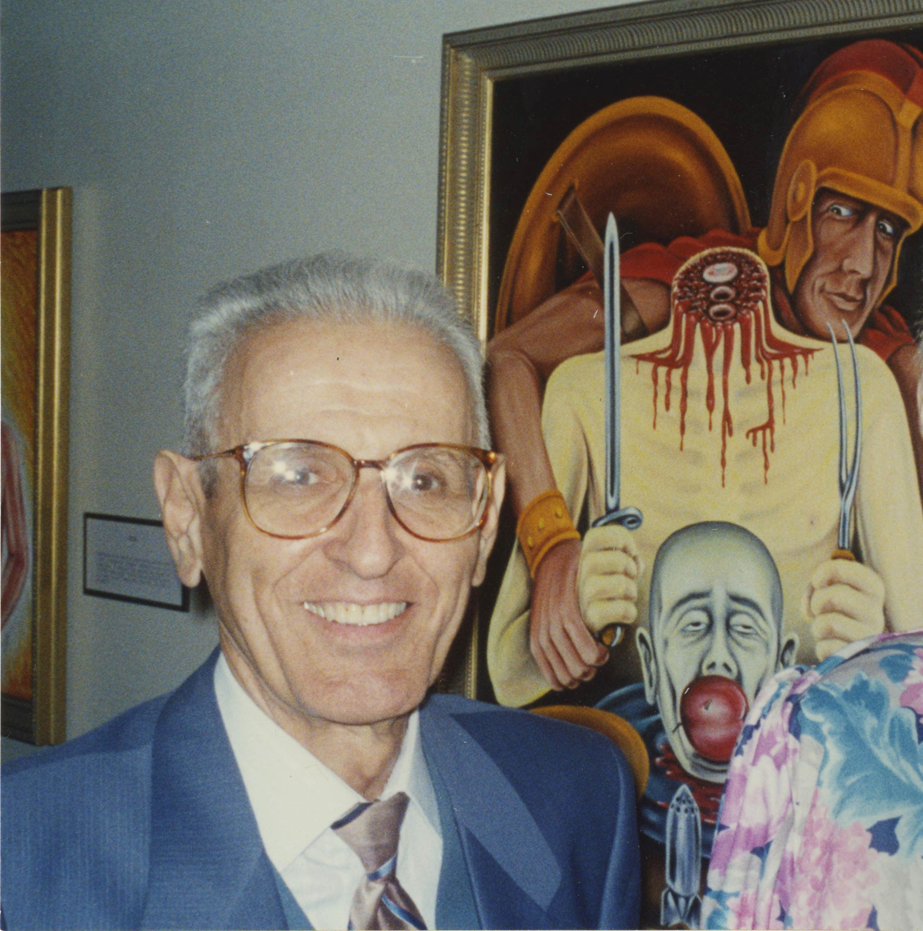 """Photograph of Jack Kevorkian, taken in front of his painting """"The Gourmet (War)"""" at Ariana Gallery in Royal Oak, Michigan. Courtesy the University of Michigan Bentley Historical Library"""