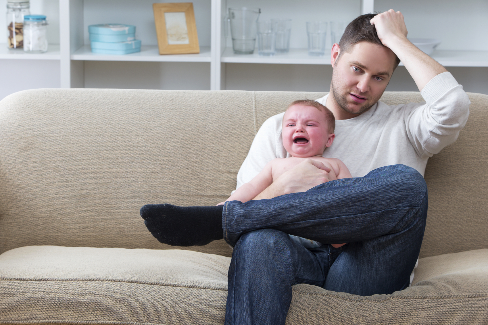 A man sitting on the couch with a crying baby. (stock image)