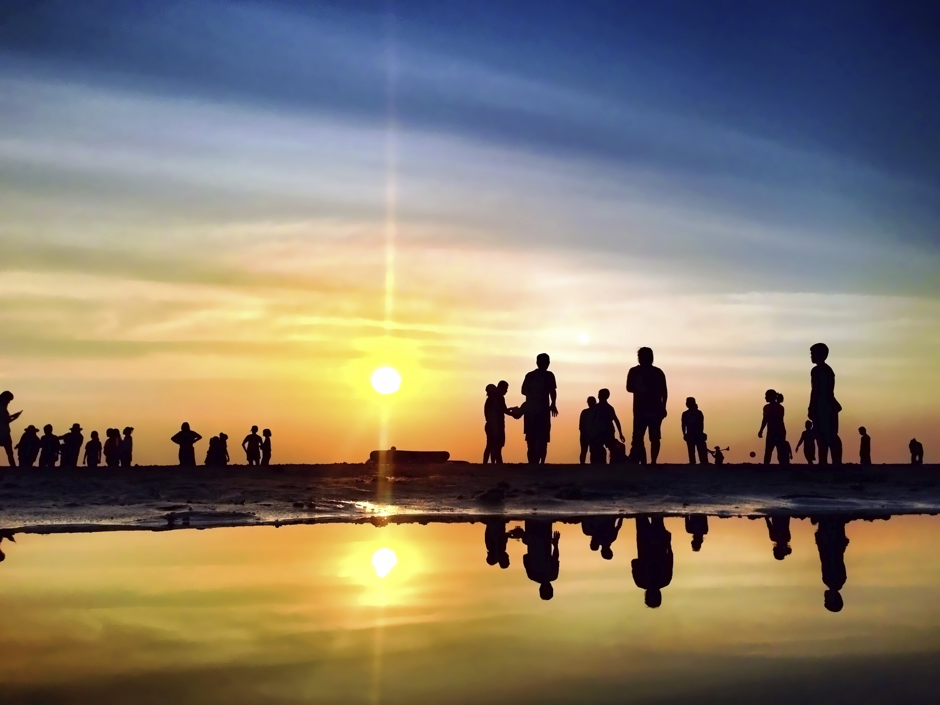 Silhouette of several people on a beach at sunset. (stock image)