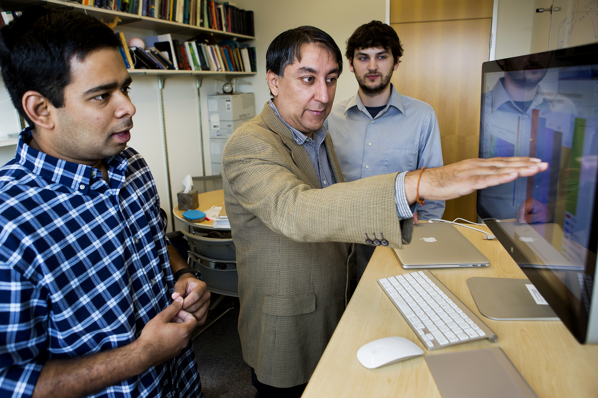 Satinder Baveja (center), University of Michigan professor of computer science and engineering, is leading a project with IBM to develop a conversational cognitive computing system that would initially serve as an automated advisor for a segment of undergrad students. Here, he discusses the project with Ananda Narayan (left) and Charles Welch (right), doctoral students and researchers in Baveja's group. Image credit: Joseph Xu