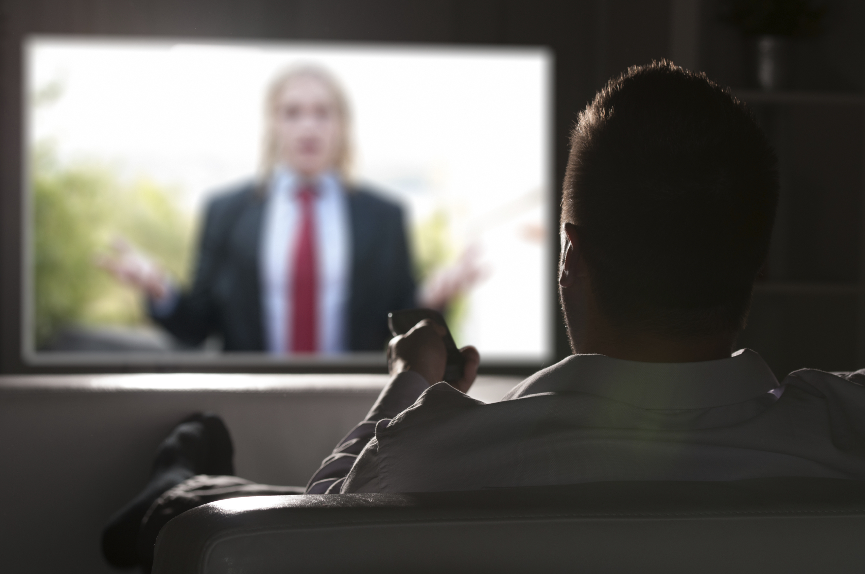 Father watching TV alone at night. (stock image)