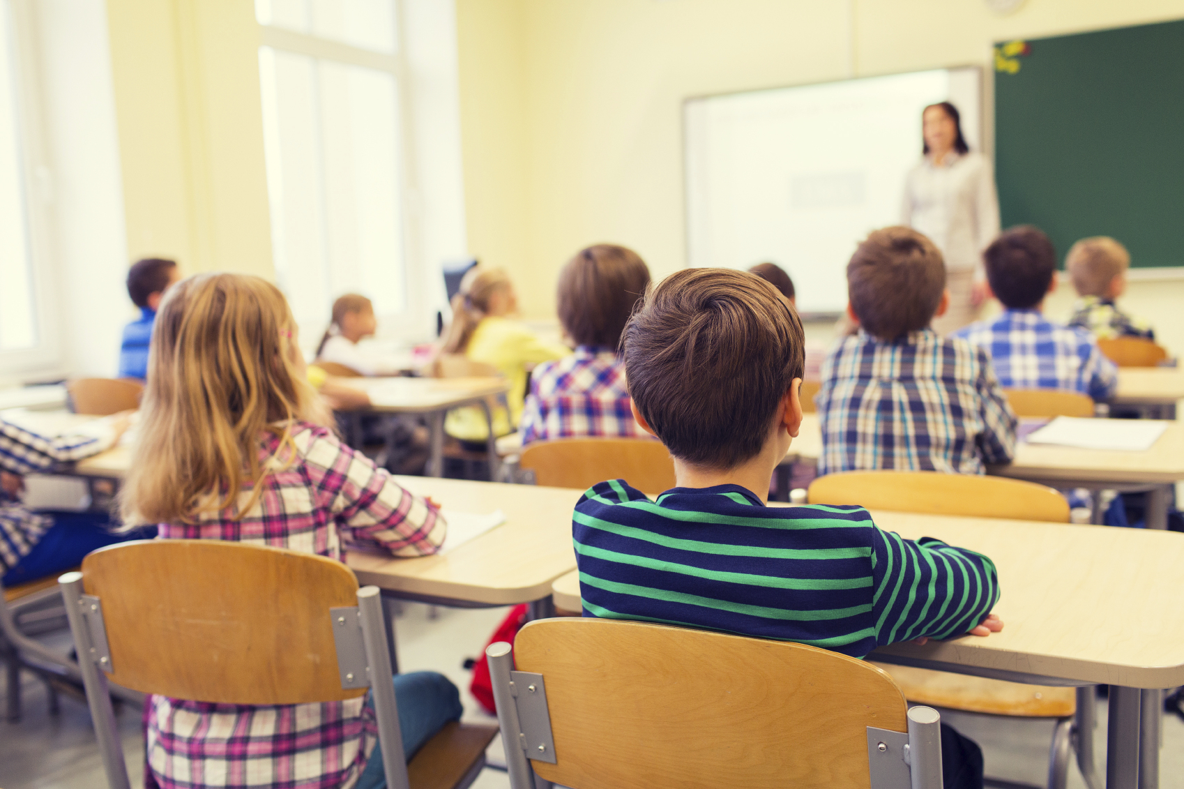 Group of school kids and teacher in classroom. (stock image)