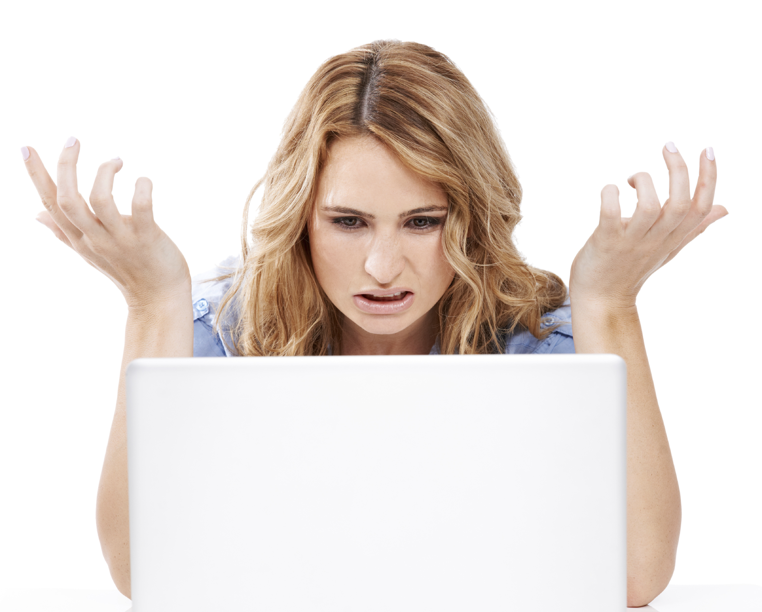 A woman holds up her hands in disugust as she looks at her laptop computer screen. (stock image)