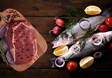 Steak on a cutting board next to a pile of fish. (stock image)
