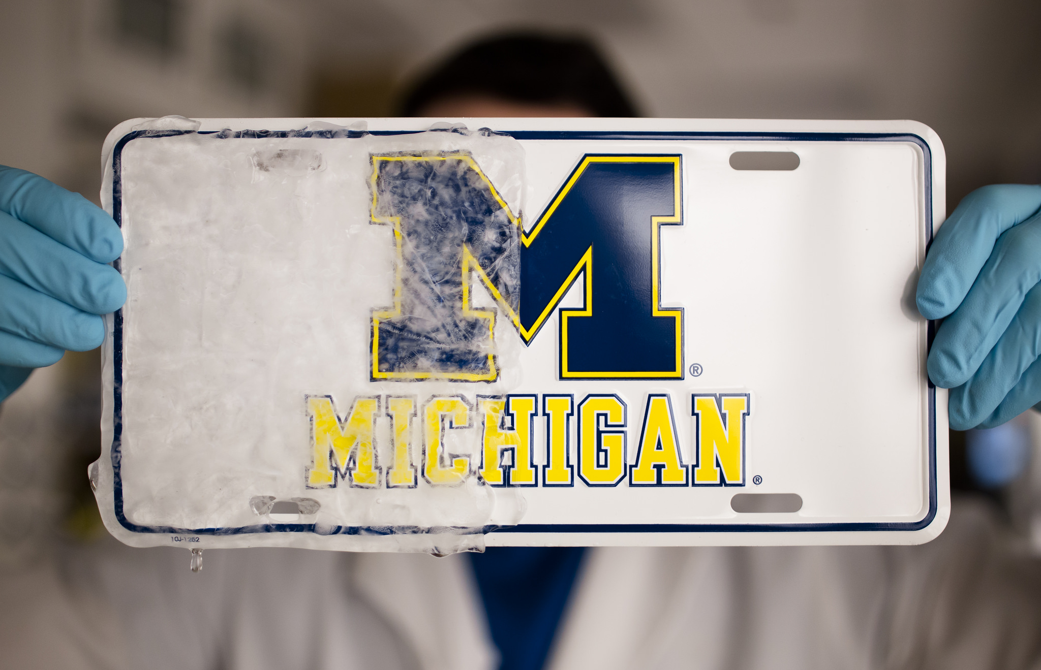 "Kevin Golovin, a graduate student in materials science and engineering at U-M, demonstrates a new rubbery material that can create ice repelling, or ""icephobic,"" coatings on a variety of materials, such as windshields or ship hulls. In this photo, the ""icephobic"" coating was applied to the right half of a license plate, preventing ice from sticking to that half after being placed in a freezer. The research is being done under the direction of Anish Tuteja, an associate professor in U-M's Department of Materials Science & Engineering. Image credit: Evan Dougherty, Michigan Engineering"