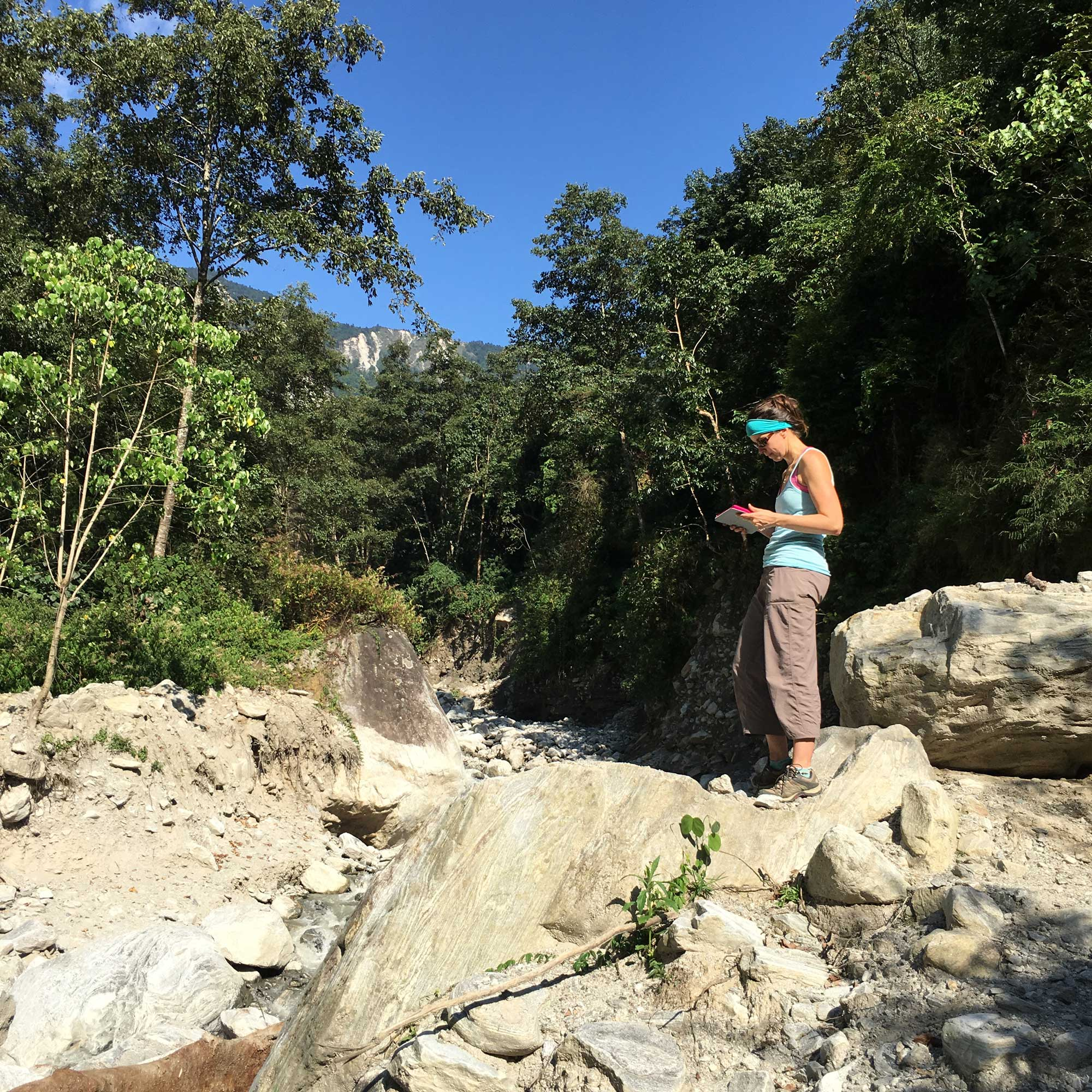 Marin Clark assessing boulders deposited during a monsoon-triggered debris flow near  Timbu, Nepal. Image credit: Dimitrios Zekkos