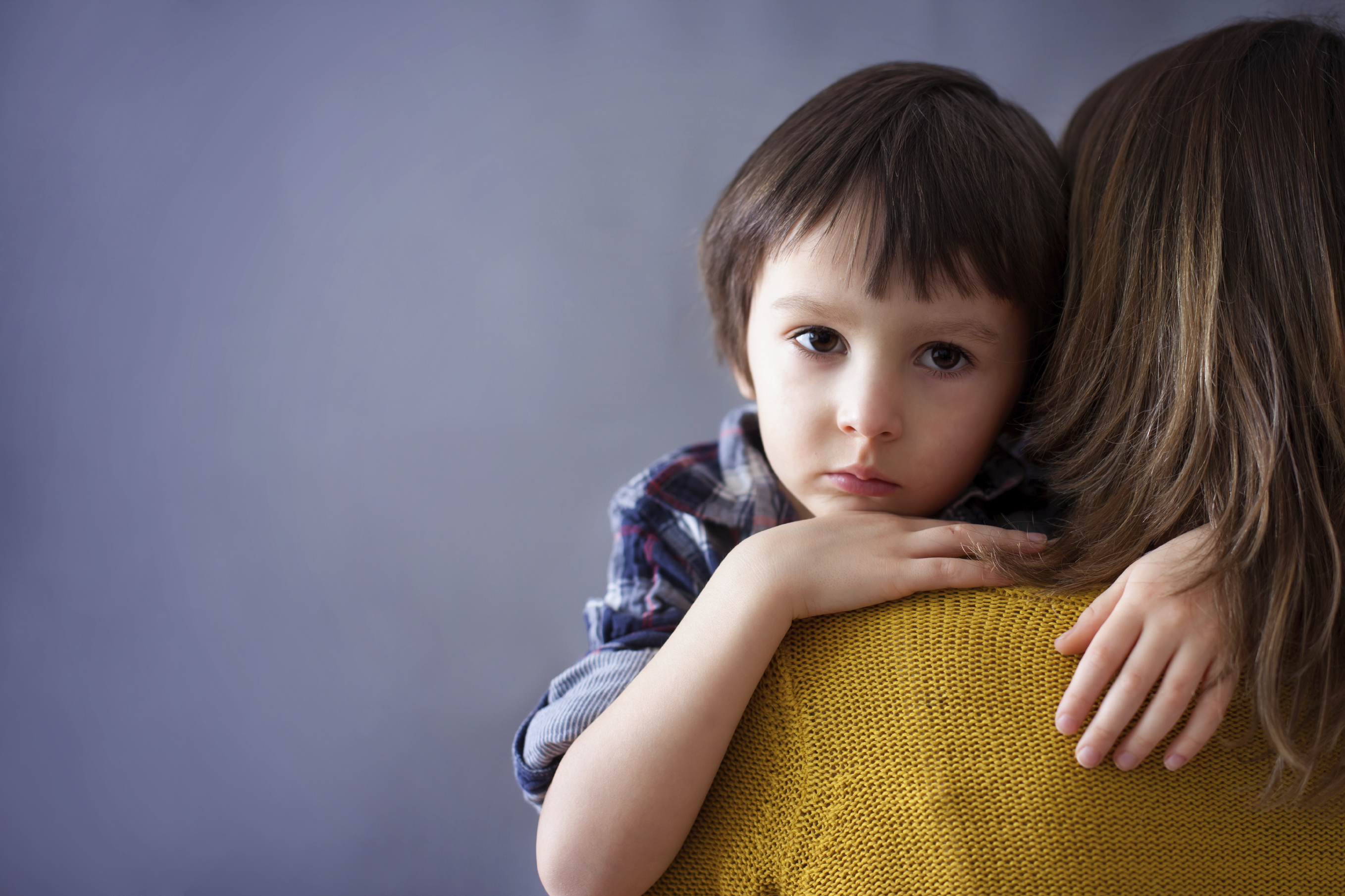 A mother hugs her son. (stock image)