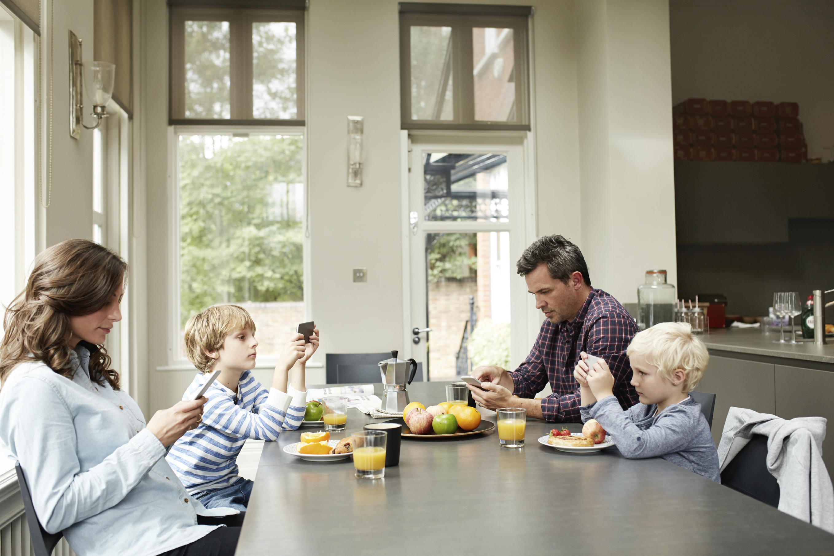 A family of four using cell phones at breakfast table. (stock image)