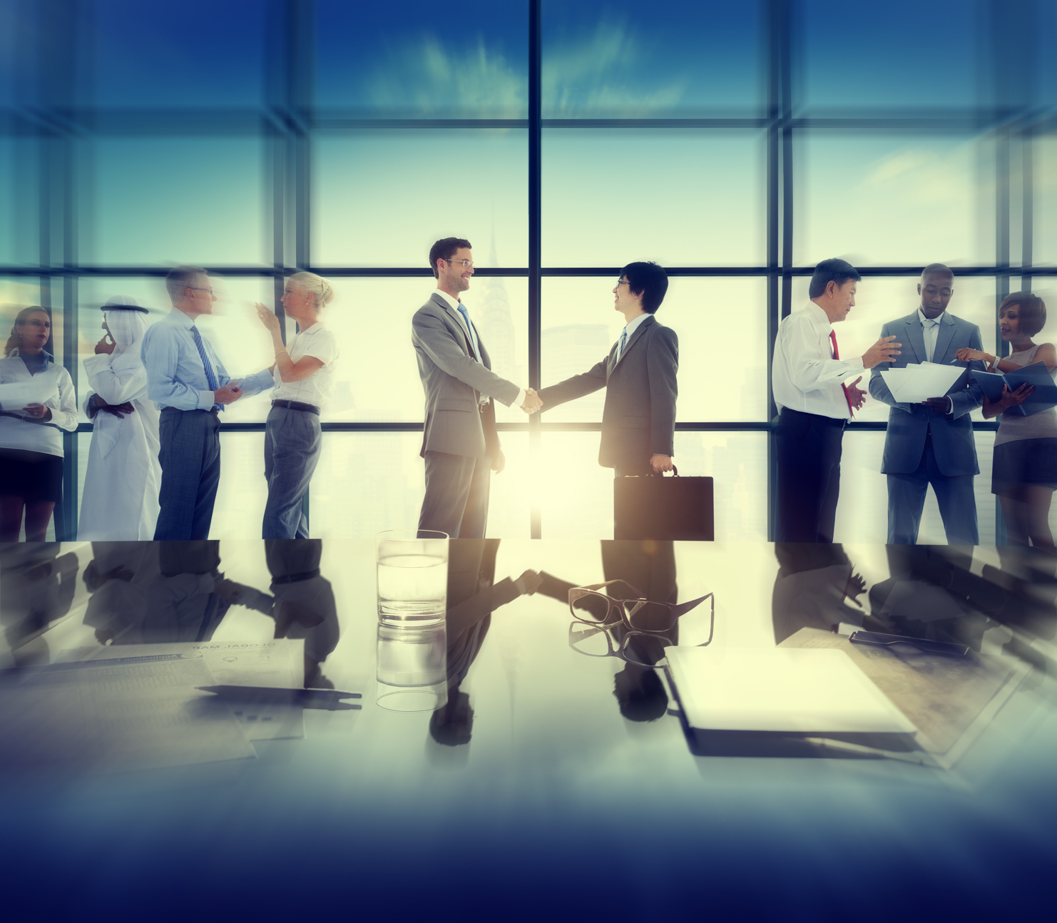 Group of business people and men handshake reflected onto table. (stock image)