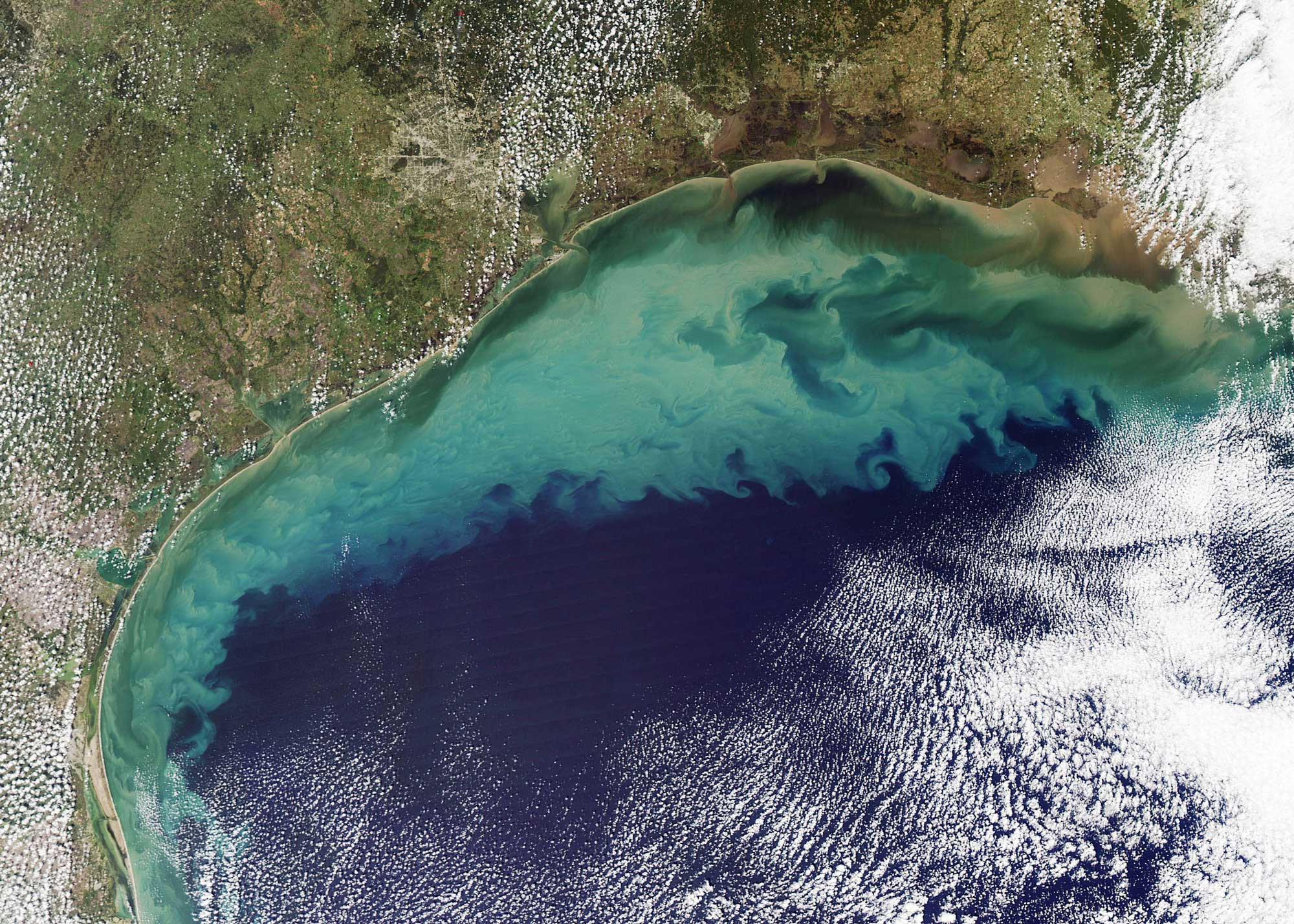 2009 satellite image of the Gulf of Mexico. Much of the dirt that colours the water is likely re-suspended sediment dredged up from the sea floor in shallow waters. The tan-green sediment-coloured water transitions to clearer dark blue water near the edge of the continental shelf where the water becomes deeper. The ocean turbulence that brought the sediment to the surface is readily evident in the textured waves and eddies within the tan and green waters. Image credit: By Jeff Schmaltz (NASA Earth Observatory) [Public domain], via Wikimedia Commons