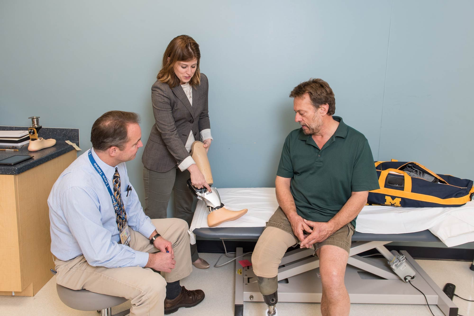Jeffrey Wensman and Deanna Gates, assistant professor, Director of the Rehabilitation Biomechanics Laboratory at the University of Michigan help fit Roger Schulte (right) with a prosthesis. Image credit: Scott C. Soderberg, Michigan Photography