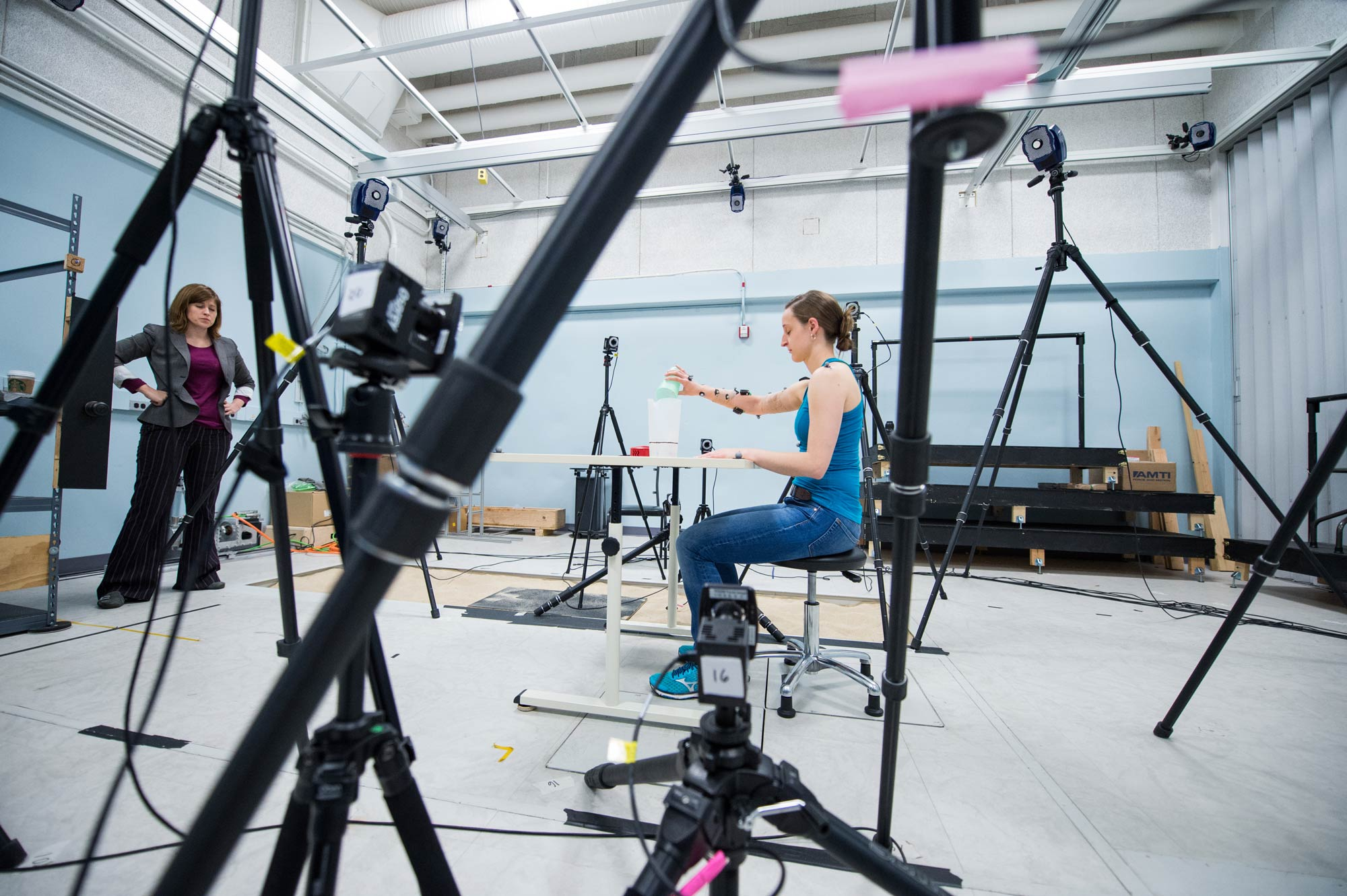 Deanna Gates, director of the Rehabilitation Biomechanics Laboratory at the University of Michigan observes as participant Kali Almdale pours a glass of water. They're recording Almdale's wrist movements using sensors. Image credit: Austin Thomason, Michigan Photography