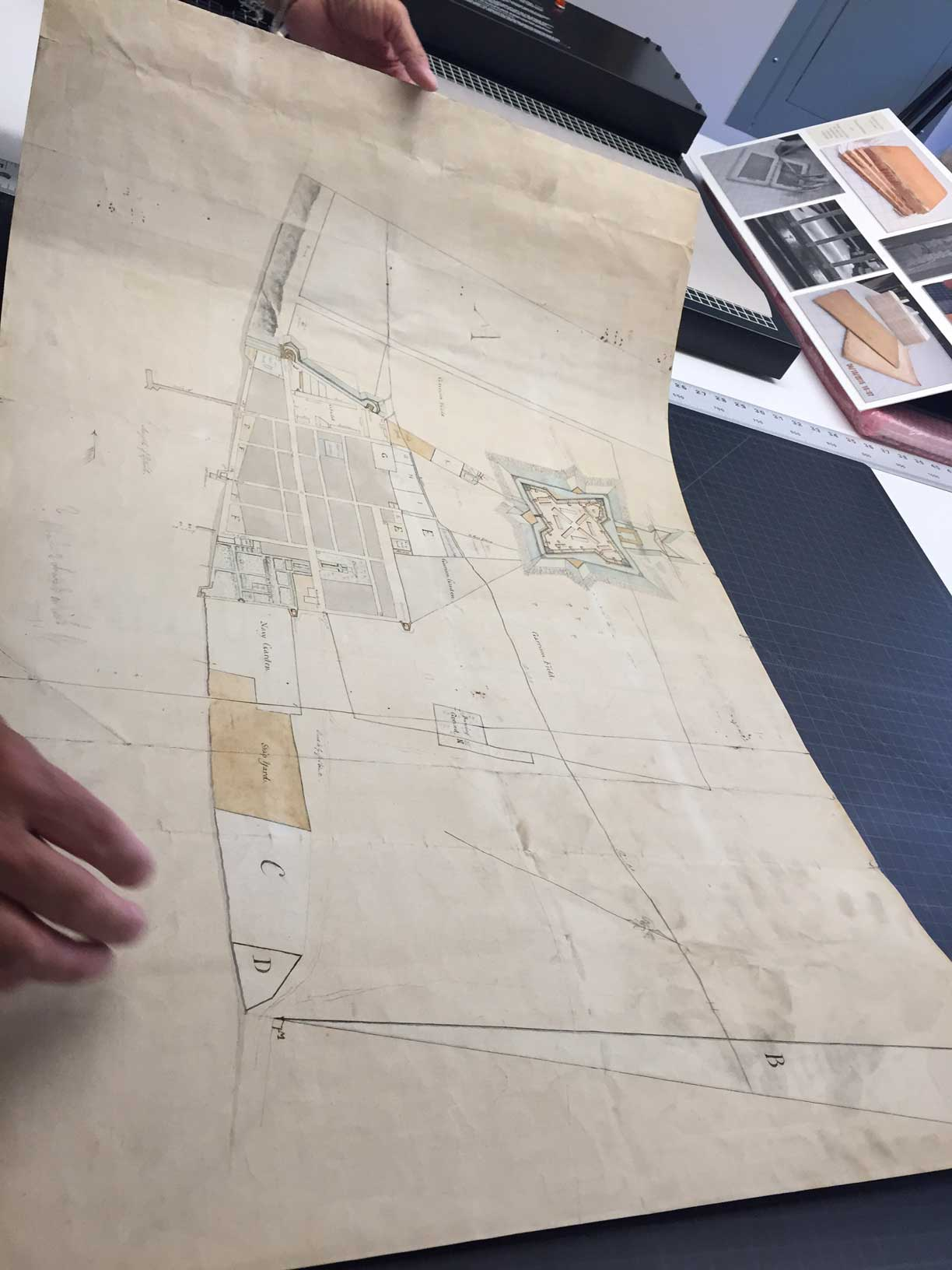 """Rough sketch of the King's Domain at Detroit,"" a 1790 manuscript plan of the city of Detroit, was discovered in a family home in Almonte, Canada. Here archivists inspect the work for the first time outside of its original frame. Image courtesy: William L. Clements Library"