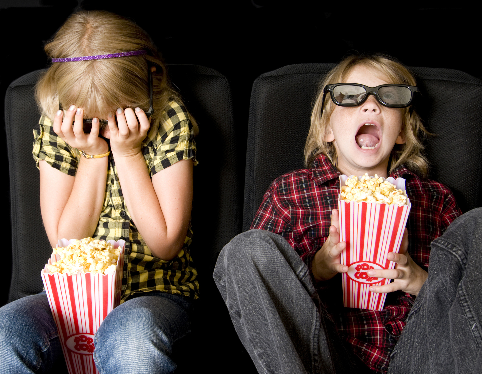 Two young girls watching a scary movie. (stock image)