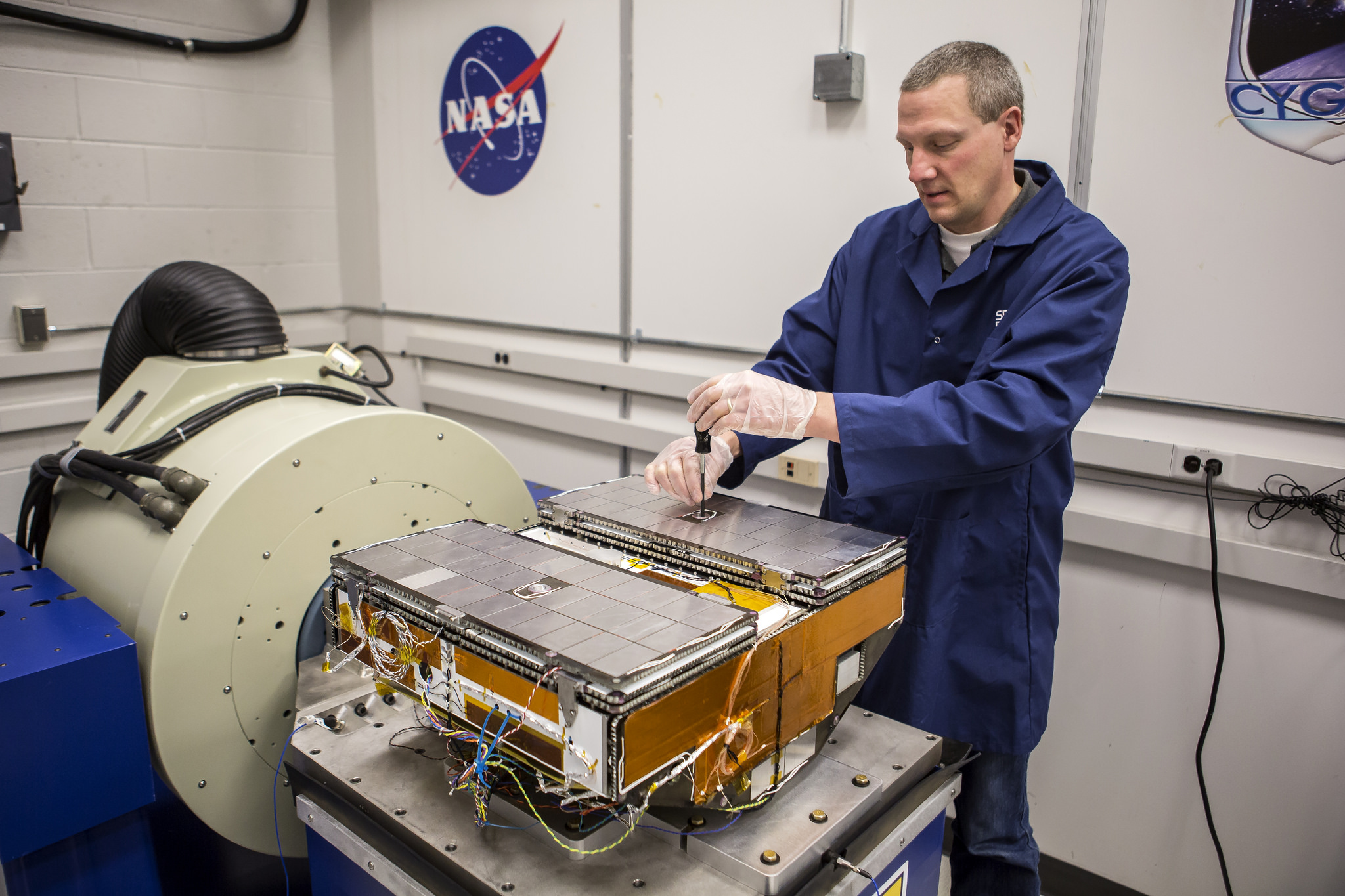 Jonathan Van Noord, research in the Department of Climate and Space Sciences and Engineering, calibrates a prototype of a CYGNSS microsatellite in the Space Research Building. Image credit: Joseph Xu, Michigan Engineering