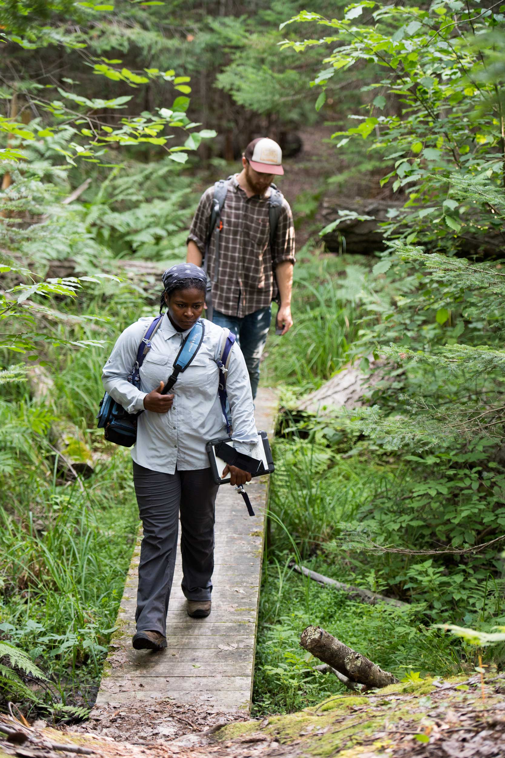 "U-M wildlife ecologist Nyeema Harris and graduate student Corbin Kuntze heading into the forest at the University of Michigan Biological Station to install ""camera traps"" to capture wildlife images. The Biological Station is one of three Michigan sites in the study, which will yield hundreds of thousands of wildlife snapshots. Image credit: Eric Bronson, Michigan Photography"