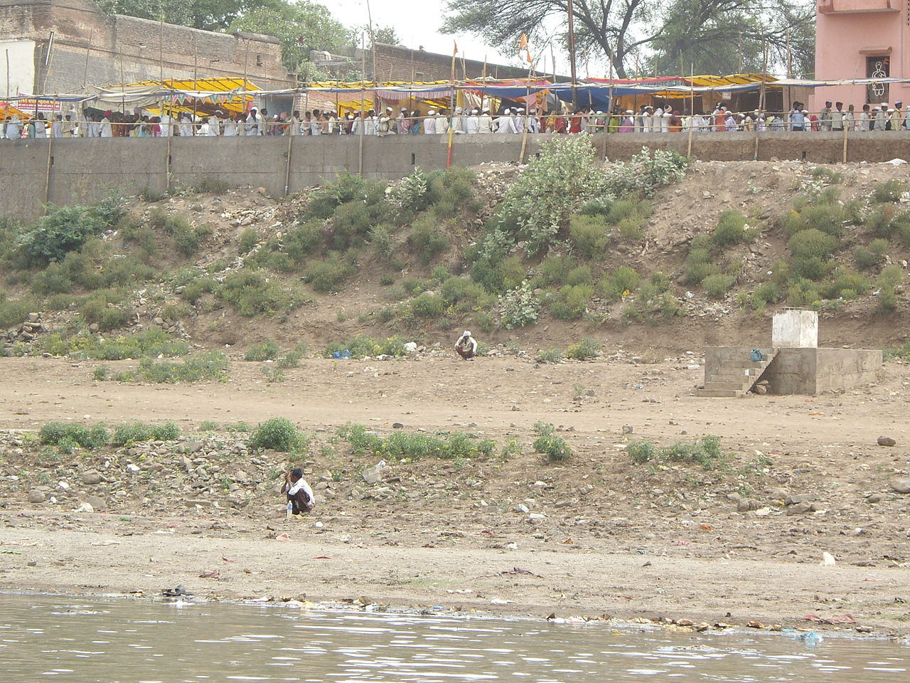 Many people defecate on the banks of the holy river. above is the line to the temple. Image credit: Yaniv Malz via Wikimedia Commons