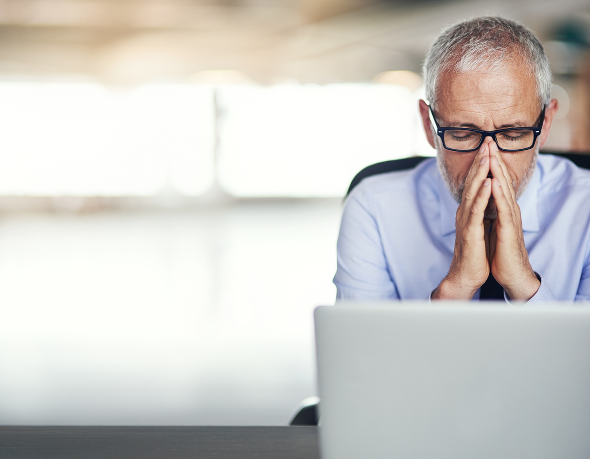 An older worker sits stressed out in front of his laptop. (stock image)