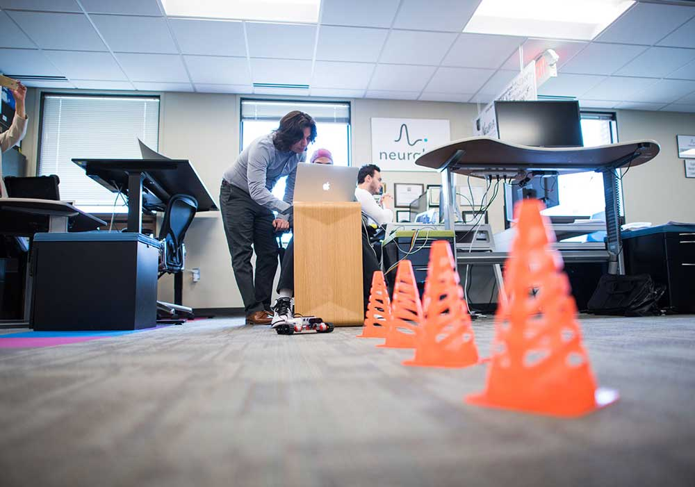 Ramses Alcaide working with a Neurable staffer demonstrates how the technology works to move a Lego Mindstorm toy car by interpreting brain activity at the startup's office space at SPARK in Ann Arbor this summer. Photo by Austin Thomason, Michigan Photography.