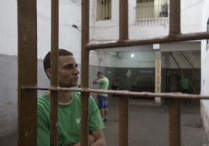 A man sits behind bars in a Brazil prison. Image credit: Levi Stroud