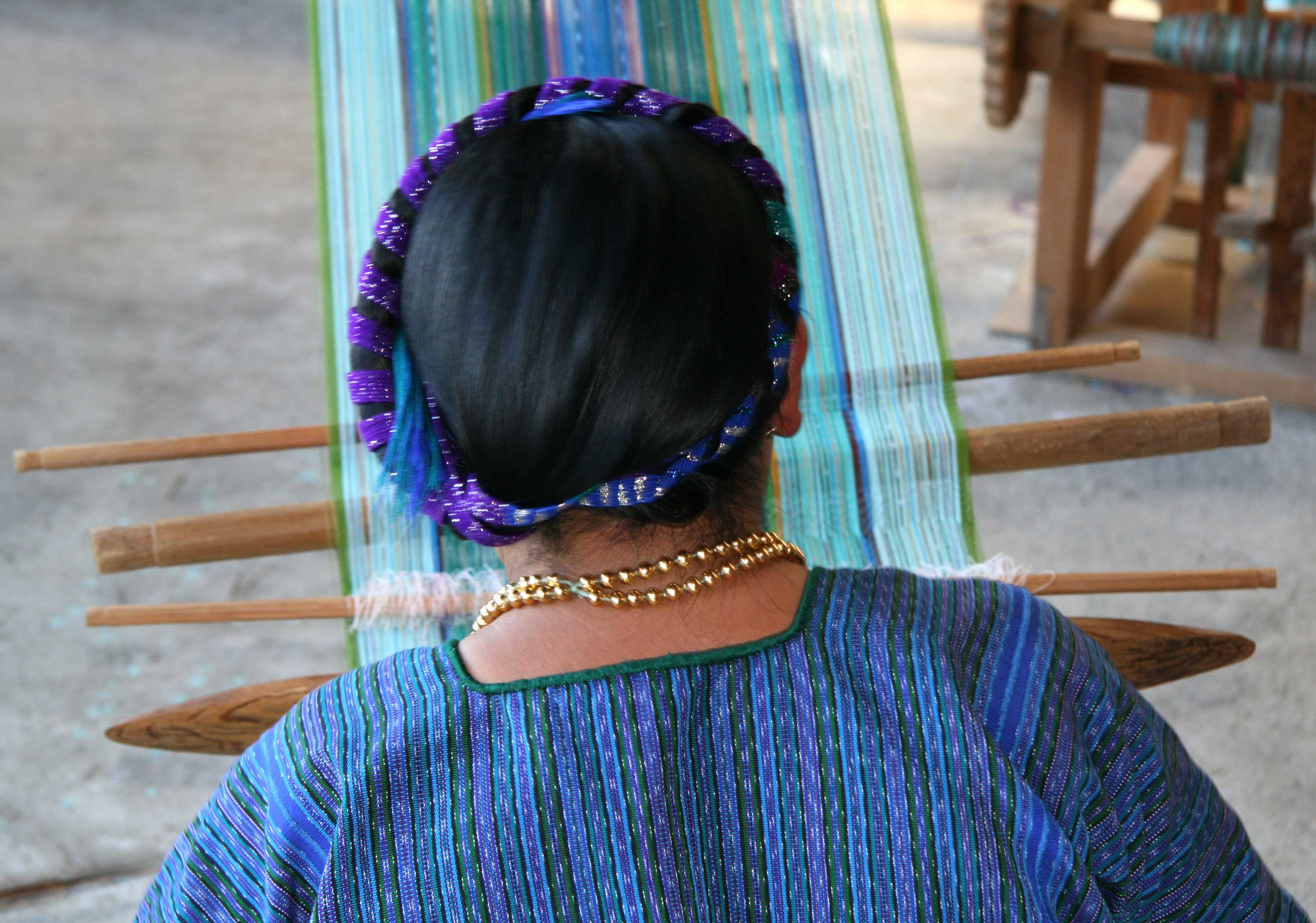 Mayan woman weaving on a traditional backstrap loom in village by the lake Atitlan, Guatemala. (stock image)