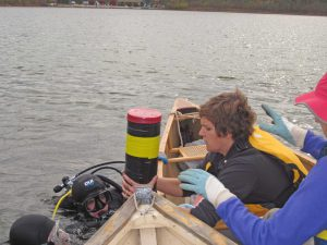 Scuba divers hand a coring device containing lake-bottom sediments to U-M biologist Mary Rogalski at a Connecticut lake. Image credit: Phoebe Zarnetske