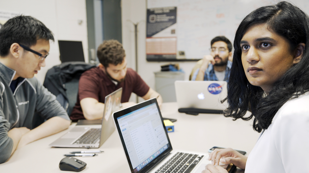 University of Michigan M-BARC team lead Hashmita Koka, a graduate student in aerospace engineering, discusses orbital dynamics of their satellite time capsule with other members of the group. Image credit: Robert Coelius