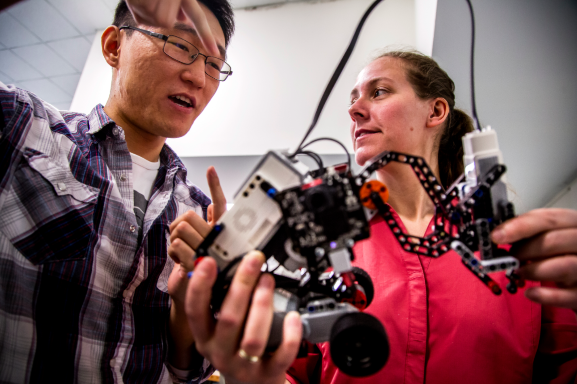Ding Zhang, ME PhD Student, and Kira Barton, ME Professor, discuss results from a recent test of a robot that uses cooperative algorithms in the HH Dow Building on March 9, 2015. The robot interacts with other robots that are installed with cooperative algorithms that Kira Barton and her research group have designed in hopes of providing a model for larger scale implementation of autonomous vehicles and robots. Image credit: Joseph Xu, Michigan Engineering Communications & Marketing