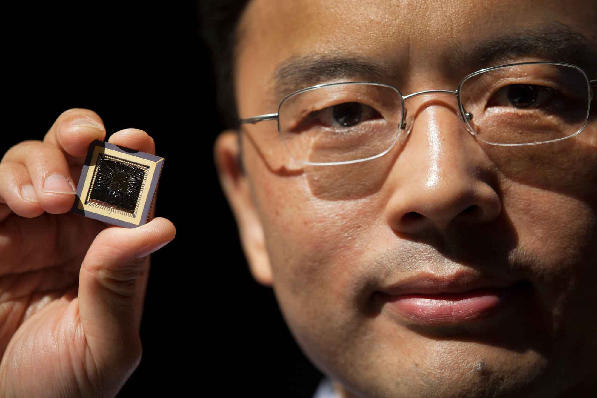 Wei Lu, Professor of Electrical Engineering & Computer Science at the University of Michigan holds a memristor chip he created.
