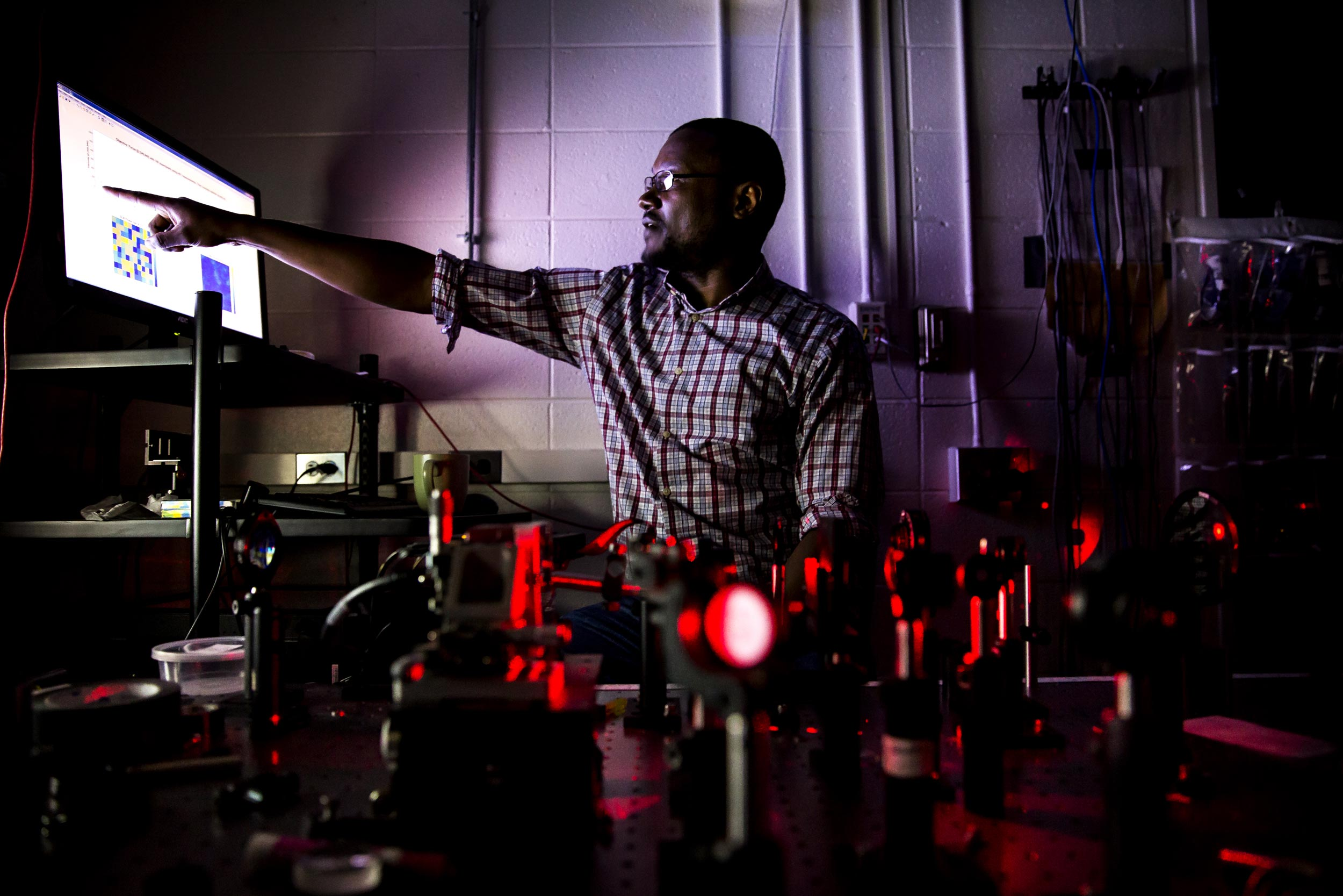 Moussa N'Gom points to a display showing how the yogurt scatters light. He hopes that the speedy algorithm developed by his team is another step toward medical imaging that can see through skin with visible light. Image credit: Joseph Xu, Michigan Engineering