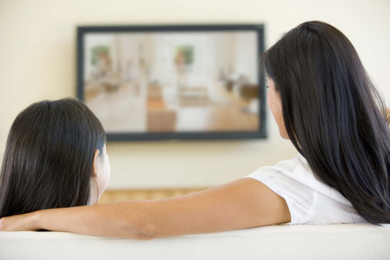 Woman and young girl in living room with television. (stock image)