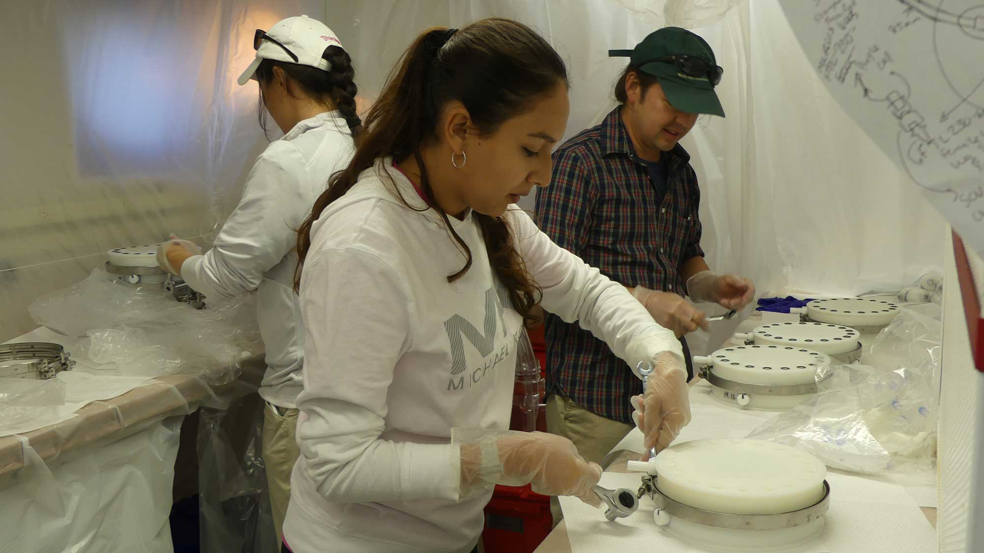 "WHOI biogeochemist Mak Saito (far right), Brianna Alanis of UTRGV (center), and Sharon Grim of Michigan open samples collected by Clio to prepare them for microbiological and biochemical analysis inside a ""clean lab."" To prevent contamination, researchers work within a temporary plastic cleanroom environment lab onboard the ship. Image courtesy: Abigail Noble"
