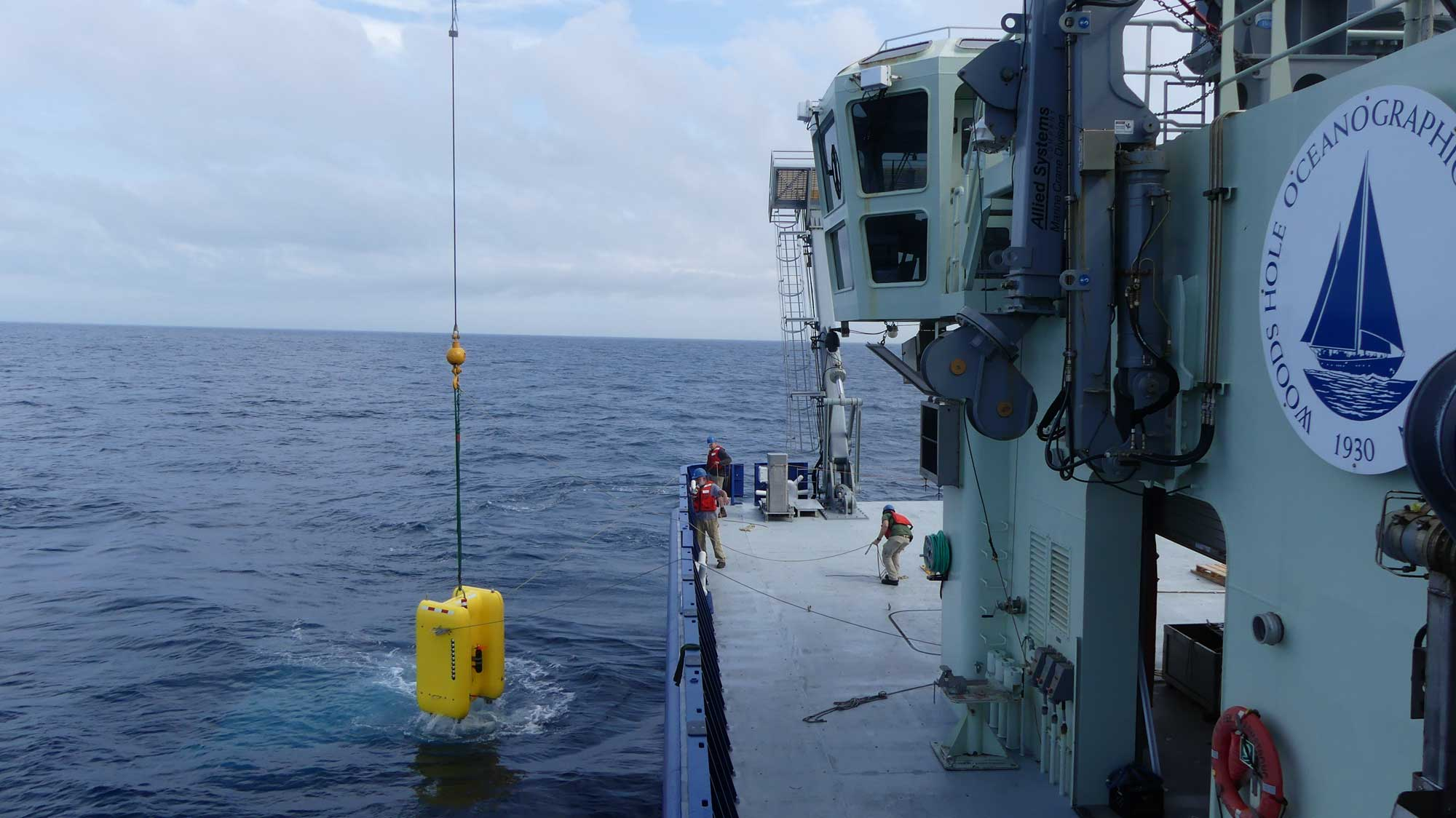 The crew aboard the R/V  Neil Armstrong  helps guide  Clio  into the water for tests at  sea. During the expedition , Clio  completed five dives, including two dives to 2,000  meters (1.2 miles), and filtered more than 1,000 liters (264 gallons) of se awater  from nine different depths. Image credit: Mak Saito, Woods Hole Oceanographic Institution