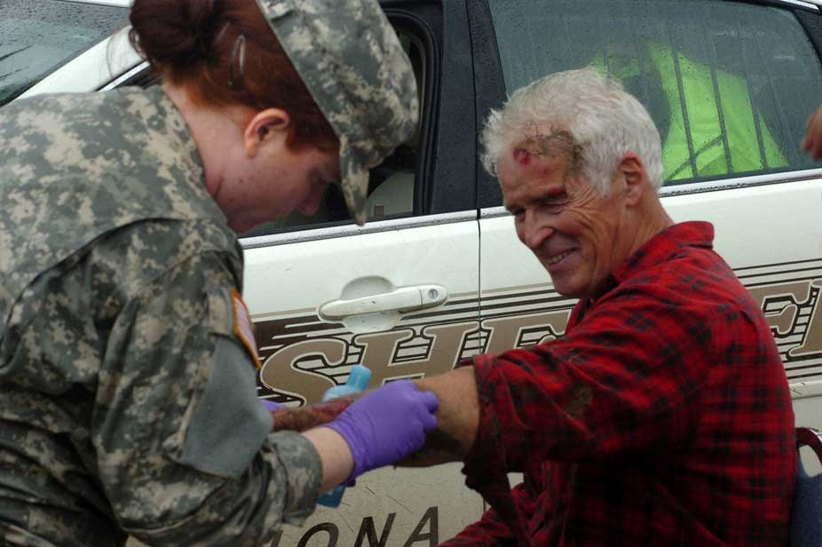 U.S. Army Spc. Pam Anderson applies first-aid medical attention to an elderly man during flood relief operations just outside of Winona, Minnesota, August 20, 2007. Image credit: Staff Sgt. Daniel Ewer, U.S. Army
