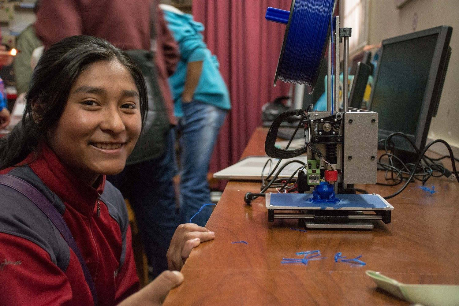 A senior student from San Francisco de Asis high school in Puno, Peru, uses a 3D  to print a prototype she designed using Fusion 360 software.
