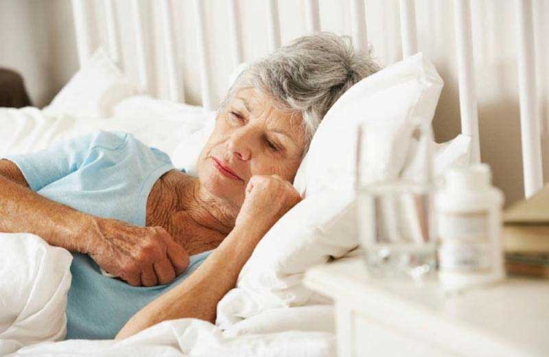 An older woman laying in bed with her eyes open. (stock image)