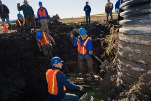 U-M paleontologists Michael Cherney, left, and Daniel Fisher dig for mammoth bones next to a sump pump at a low point in one of farmer James Bristle's fields. Installation of the drainage system led to the discovery of mammoth bones in 2015.