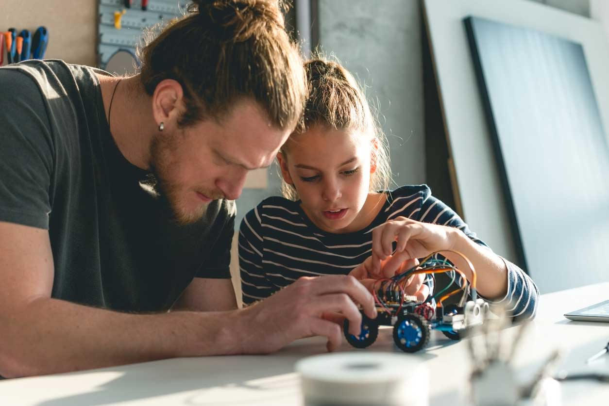 A father building a robot with his daughter. (stock image)